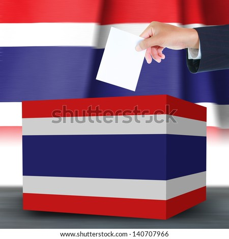 Hand holding ballot and box with the Thailand flag in the background - stock photo