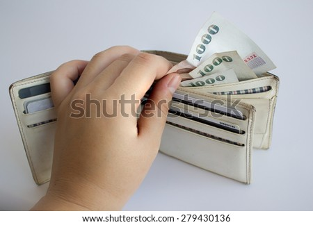 hand holding Banknotes of Thailand in wallet on white background - stock photo