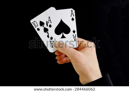 hand holding best classic winning blackjack combination ten and ace of spades - stock photo