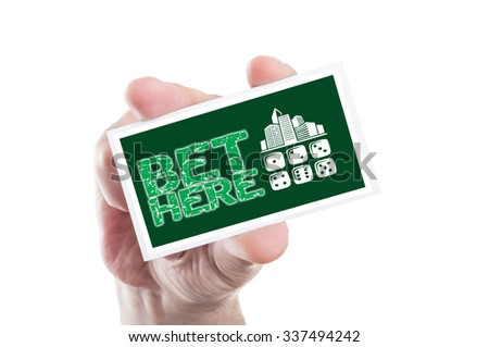 Hand holding bet here card as online betting concept with casino shape - stock photo