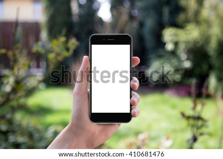 Hand holding black smartphone with blank screen against blurred garden background - stock photo