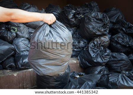 hand holding black trash bags - stock photo