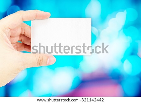 Hand holding blank business card with blur blue bokeh light background ,Business concept