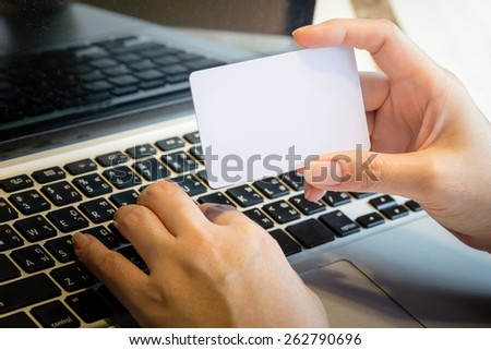 Hand Holding Blank Credit Card Over Laptop Online Shopping Concept - stock photo