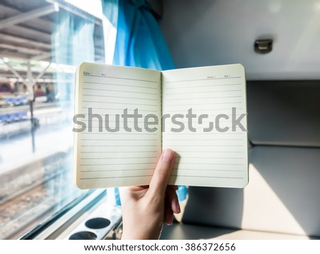 Hand holding blank notebook template on a train, Seat opposite is background - stock photo