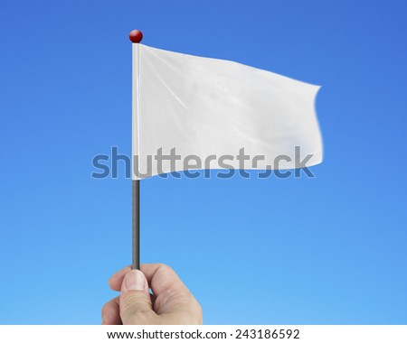 hand holding blank white flag isolated on blue background - stock photo