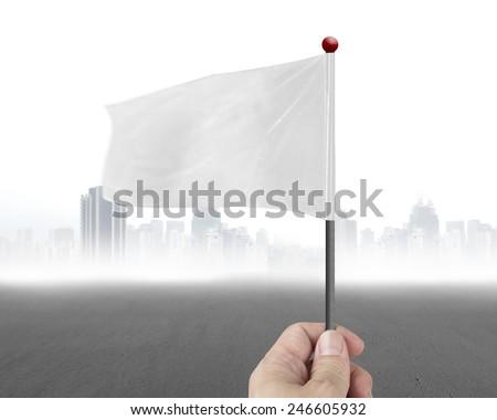 hand holding blank white flag with gary cityscrape background - stock photo