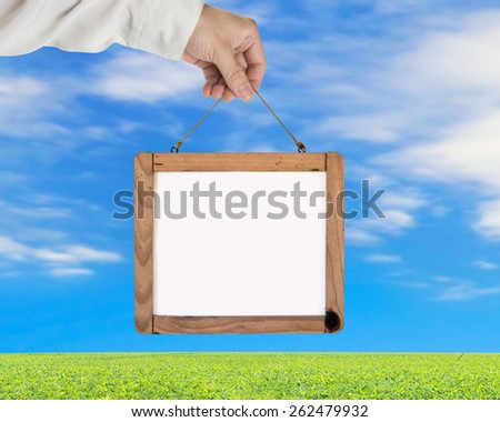 Hand holding blank white message board with blue sky clouds green grass background - stock photo