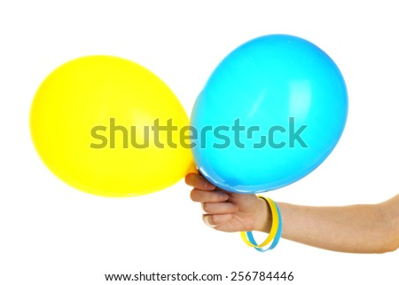 Hand holding blue and yellow balloons, isolated on white  - stock photo