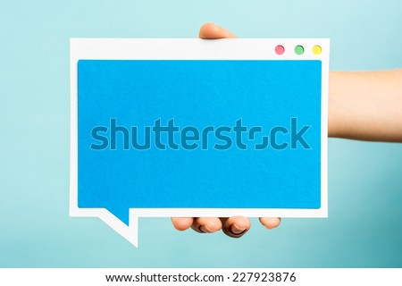Hand holding blue speech bubble with flat design, mock-up. Internet concept. - stock photo