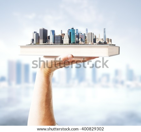 Hand holding book with city on blurry background. 3D Rendering - stock photo