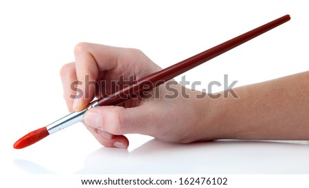 Hand holding brush with red paint isolated on white - stock photo