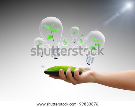 Hand holding bulb with green tree - stock photo