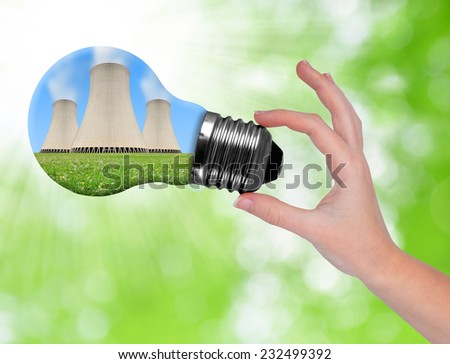 Hand holding bulb with nuclear power plant on green background - stock photo