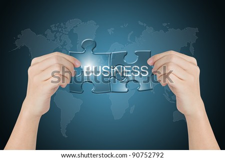 hand holding business connected jigsaw puzzle with world map background - stock photo