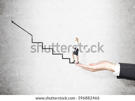 Hand holding businesswoman starting to climb stairs drawn on concrete wall. Concept of career growth. - stock photo