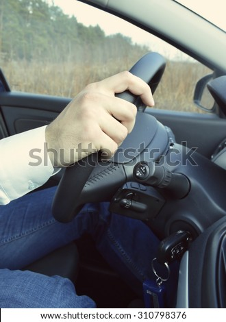 Hand holding car key for starting the car.Male hand with car key on car background