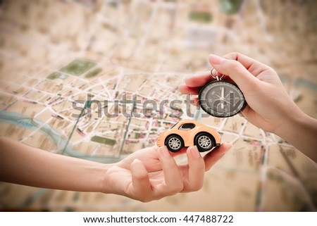 hand holding car model and compass with blur road map background - stock photo