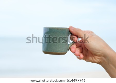 Hand holding ceramic cup of coffee on sea and sky background, with peace and joy concept