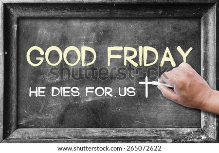 """Hand holding chalk and writing text """"Good Friday He Dies For Us"""" on blackboard. Christmas Thankful Adoration Glorify Peace Evangelical Hallelujah Blessing Amen Hope Religion Hosanna Love Trust concept - stock photo"""
