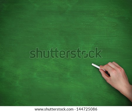 Hand holding chalk on green background