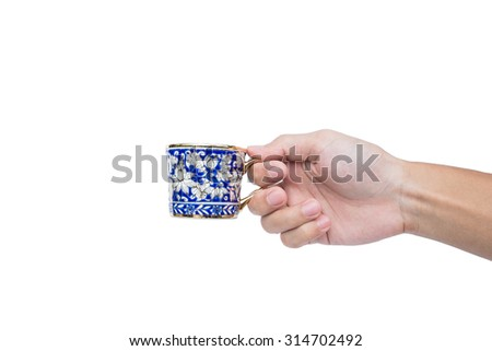 Hand holding classic luxury porcelain cup, isolated on white background - stock photo