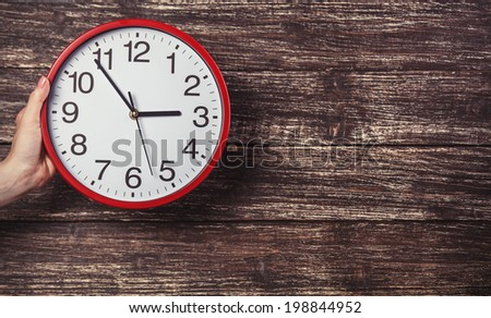 Hand holding clock on wooden background. - stock photo