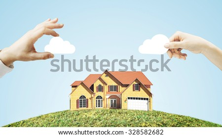 hand holding cloud over house - stock photo