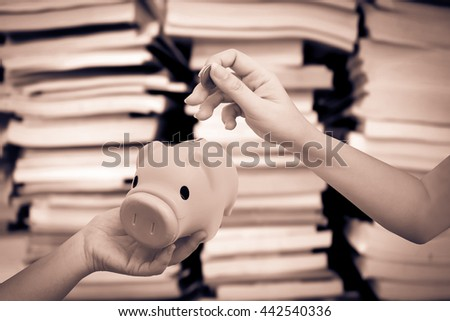 hand holding coin to piggy bank with blur stacking book background