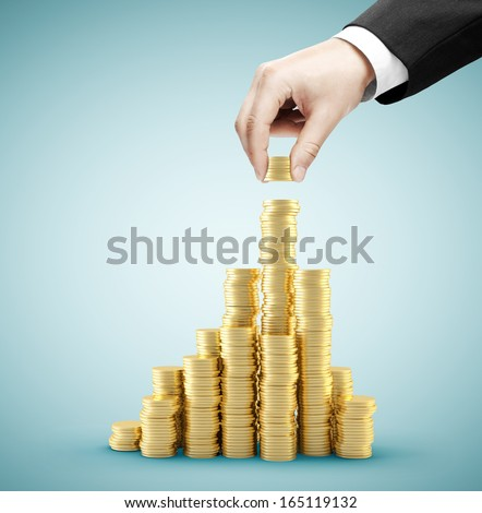 hand holding coins and build coin chart - stock photo