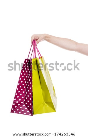 Hand holding colorful shopping bags, isolated on white background