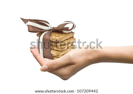 hand holding cookies with ribbons as a present isolated on white - stock photo