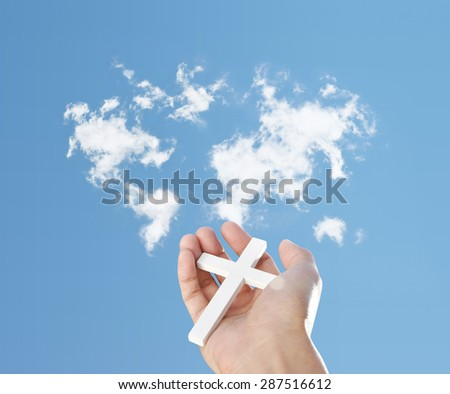 Hand holding cross and clouds map - stock photo