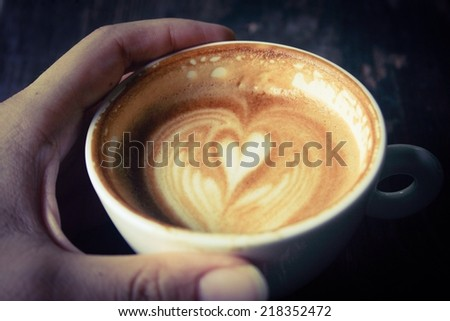 Hand holding cup of latte or cappuccino already sip  , retro vintage filter effect  - stock photo