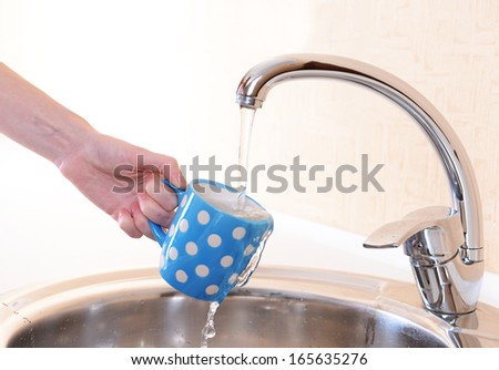 Hand holding  cup of water poured from  kitchen faucet - stock photo