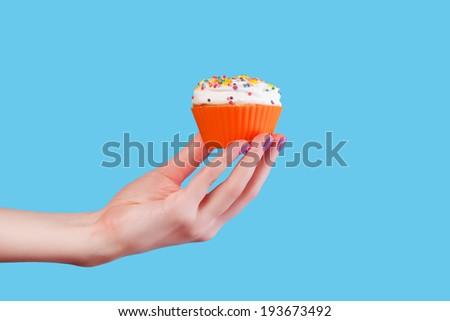 Hand holding cupcake on blue background - stock photo