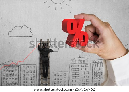 Hand holding 3D red percentage sign with businessman drawing trend chart on doodles wall background - stock photo