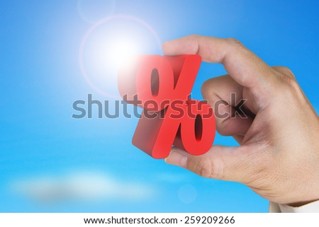 Hand holding 3D red percentage sign with sky sunlight background - stock photo