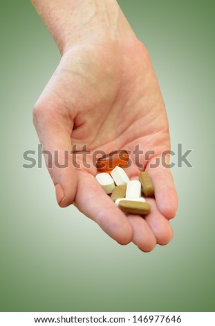 hand holding daily supplements, vitamins or medication on green background - stock photo