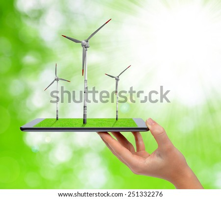 Hand holding digital tablet with a wind turbines.  Green energy concept.  - stock photo