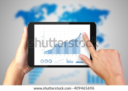Hand holding digital tablet with business graph on display