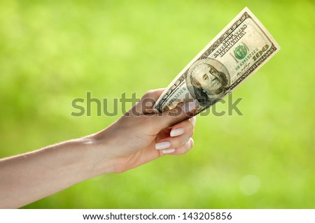 Hand holding dollar banknote on light green background - stock photo