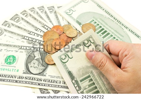 Hand holding dollar bills with coins and dollar bill are background. - stock photo