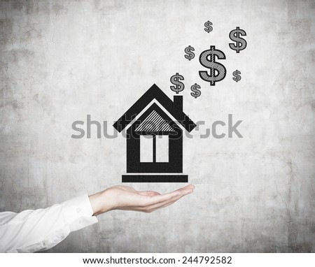 hand holding drawing house with dollars - stock photo
