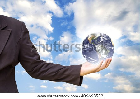 hand holding Earth on sky background. Elements of this image are furnished by NASA