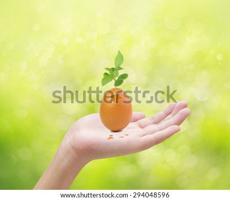 Hand holding egg and plant , concept - stock photo
