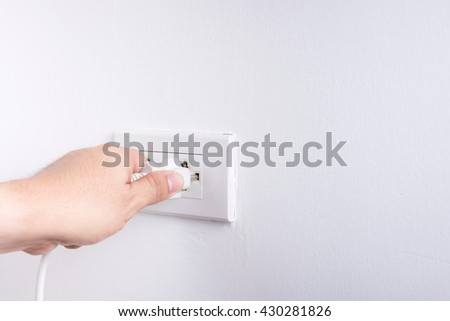 Hand holding electric plug isolated on white background