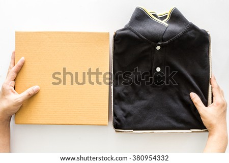 Hand holding empty  box and black shirt on white background - stock photo