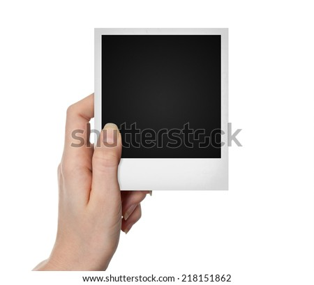 Hand holding empty polaroid vintage photo on white background - stock photo