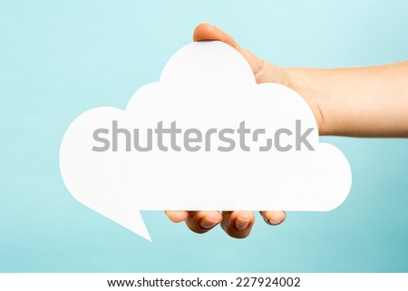 Hand holding empty speech bubble cloud on blue background. Internet concept. - stock photo